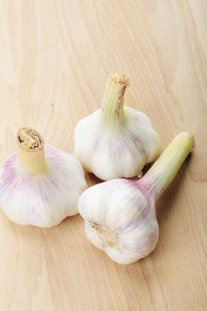 Three garlic bulbs on wooden board above view Stock Photo