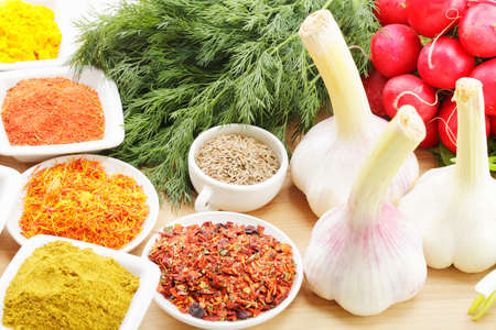 grinded: Spices in abundance and vegetables on wooden board closeup photo Stock Photo