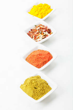 grounded: Different grounded spices in a row  on tablecloth above view Stock Photo