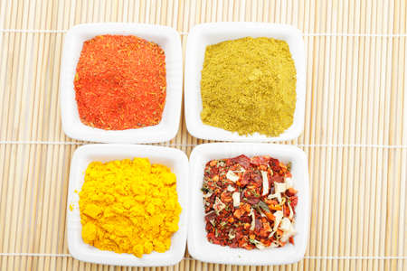 Vaus spices in white dishes on straw mat above view Stock Photo - 8176653