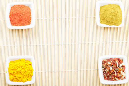 Straw mat with four dishes in corners filled with spices photo