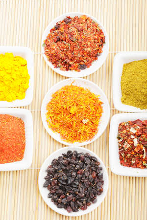 Various grounded spices in a rows on straw mat above view Stock Photo - 8176658
