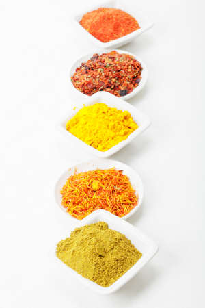 Alternation of grounded spices in a row  on tablecloth above view