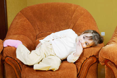 cosiness: Cute little girl relaxed in brown chair indoors