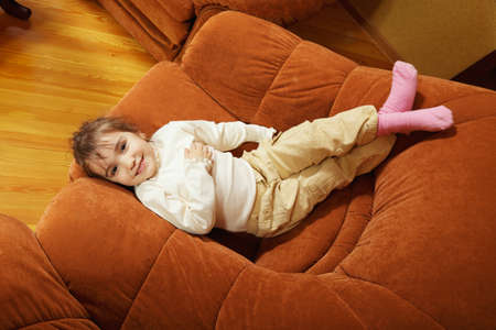 cosiness: Little smiling girl laying down in big chair above view