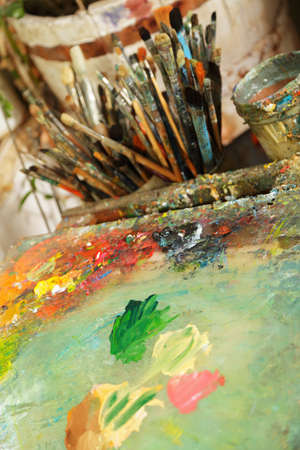 Palette with mixed paints against paintbrush set closeup photo Stock Photo - 9224497