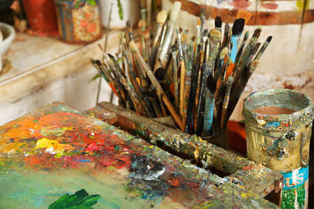 smeared: Palette and paintbrushes soiled with paints closeup photo