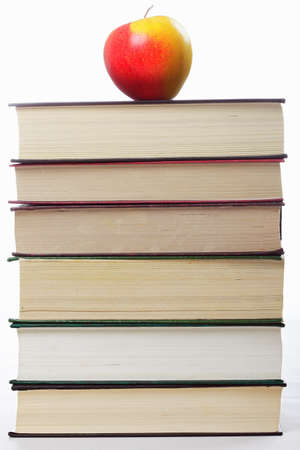 Stack of books with apple on top against light background Stock Photo - 9224499