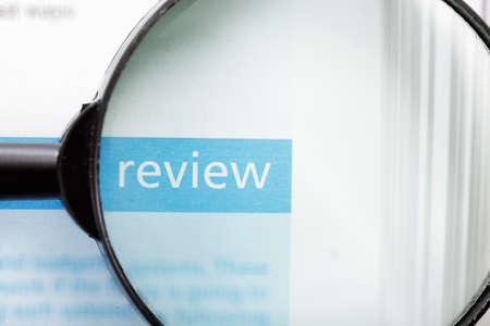Review word printed on page seen through magnifier Stock Photo