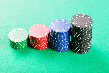Various stacked poker chips on green cloth photo