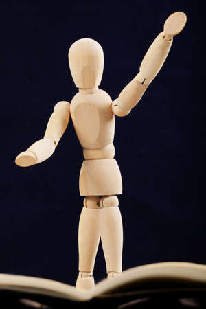 creativeness: Wooden conductor doll against dark background Stock Photo