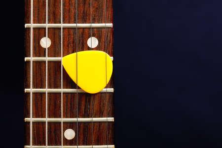 Guitar pick between strings against dark background Stock Photo