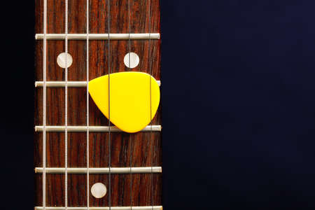 Guitar pick between strings against dark background Stock Photo