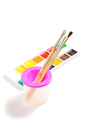 Paintbrushes and box of aquarelle paints against white Stock Photo - 9284822