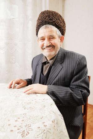 hoariness: Happy senior man in sheepskin hat sitting at table