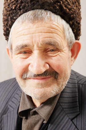 grayness: Facial portrait of elderly man in brown sheepskin hat