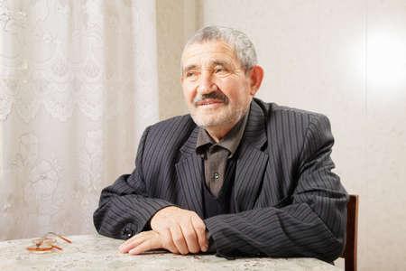 grayness: Pensive senior man sitting at table