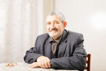 grayness: Senior man sitting at table indoors