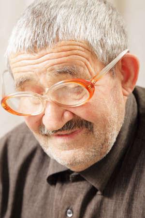 grayness: Uomo anziano in occhiali da vista guardando gi� closeup foto Archivio Fotografico