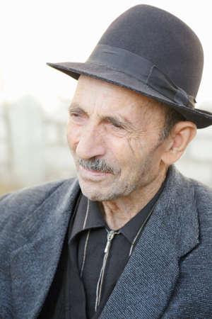 grayness: Portrait of elderly man in hat looking sideways