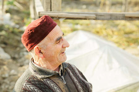 grayness: Senior man in red cap sideview photo