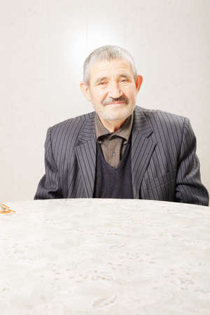 Senior man in striped jacket sitting at table Stock Photo