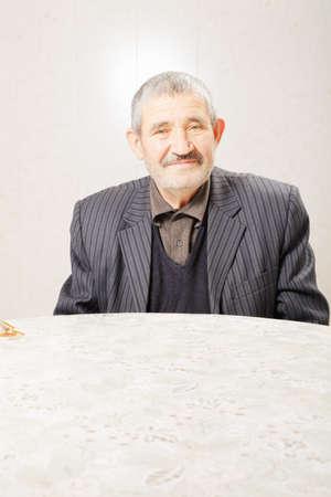 grayness: Senior uomo in giacca a righe seduto al tavolo