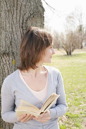 looking sideways: Young woman with book at tree looking sideways Stock Photo