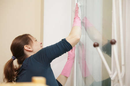 Smiling woman cleaning window sideview Stock Photo