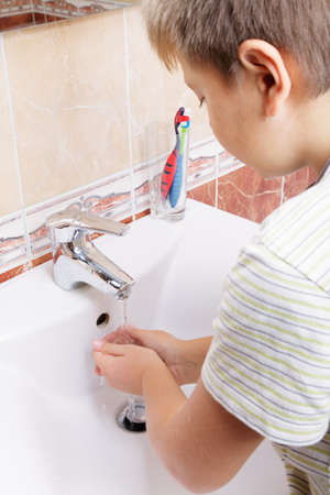 Kid washing hands over basin sideview