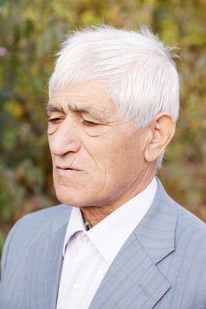 Portrait of pensive senior man in formal wear photo
