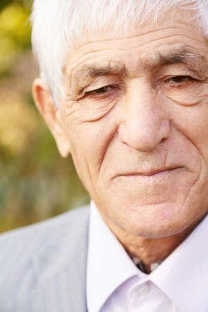 Closeup outdoor portrait of serious caucasian senior man photo