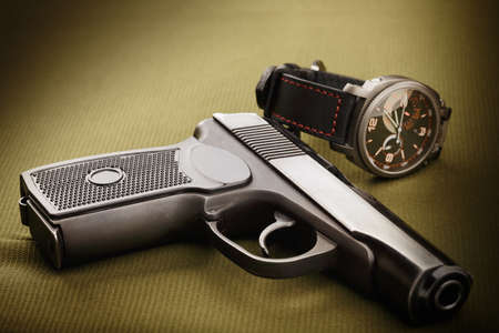 Gun and watch on cloth closeup photo
