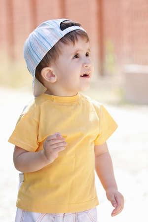 looking sideways: Little kid in yellow shirt looking sideways outdoors Stock Photo
