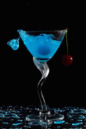 dark cherry: Splashing blue cocktail with cherry against dark background