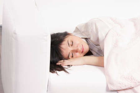 Napping young brunette woman tuck with plaid Stock Photo - 10044244