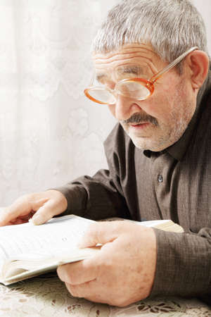 Senior gray-haired man reading book indoors