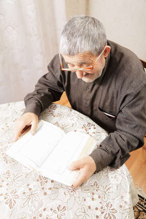 Senior man reading book at table indoors above view