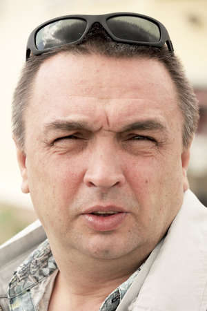 squinting: Portrait of middle-aged caucasian man squinting in sunlight