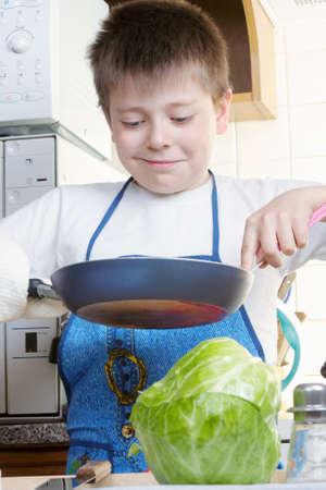 fryingpan: Smiling kid at kitchen with frying-pan