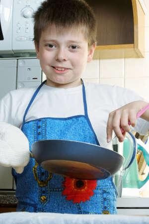 fryingpan: Positive kid at kitchen with frying-pan