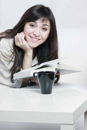 Young smiling brunette woman in casual reading on white couch closeup photo Stock Photo - 10668050