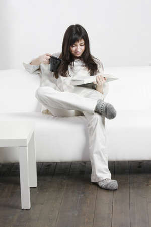 Young brunette woman in casual with cup reading book while sitting on couch photo