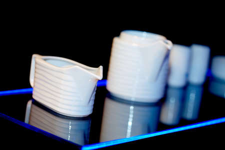 creamer: Creamer and other dishware on glass shelf lit in blue Stock Photo