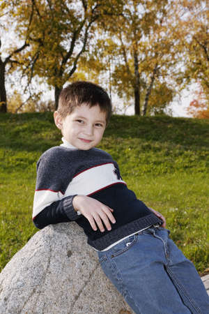 Caucasian boy leaning on stone in autumn park photo