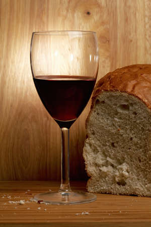 Wine and bread over wooden planks photo