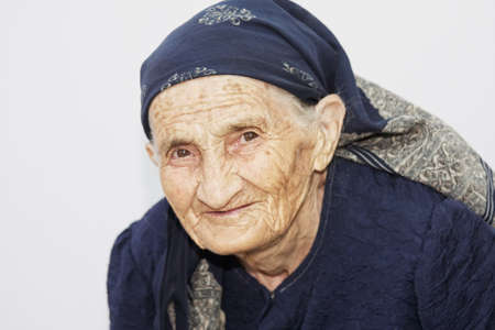 Cute senior woman against wall photo