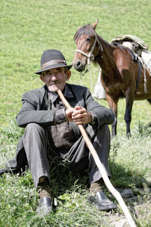 Elderly man with stick sitting on grass Stock Photo - 11307809