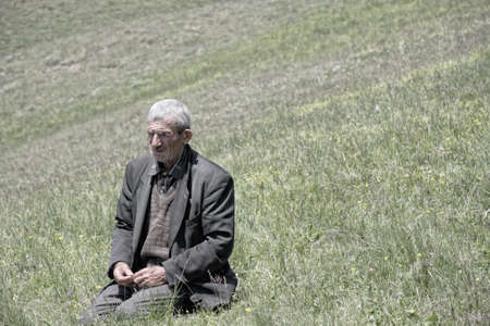 Senior man sitting on his knees in meadow photo