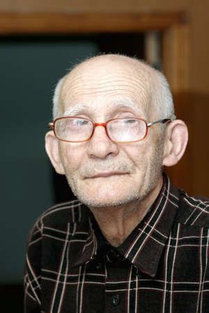 Elderly man in eyeglasses looking to camera indoor portrait photo